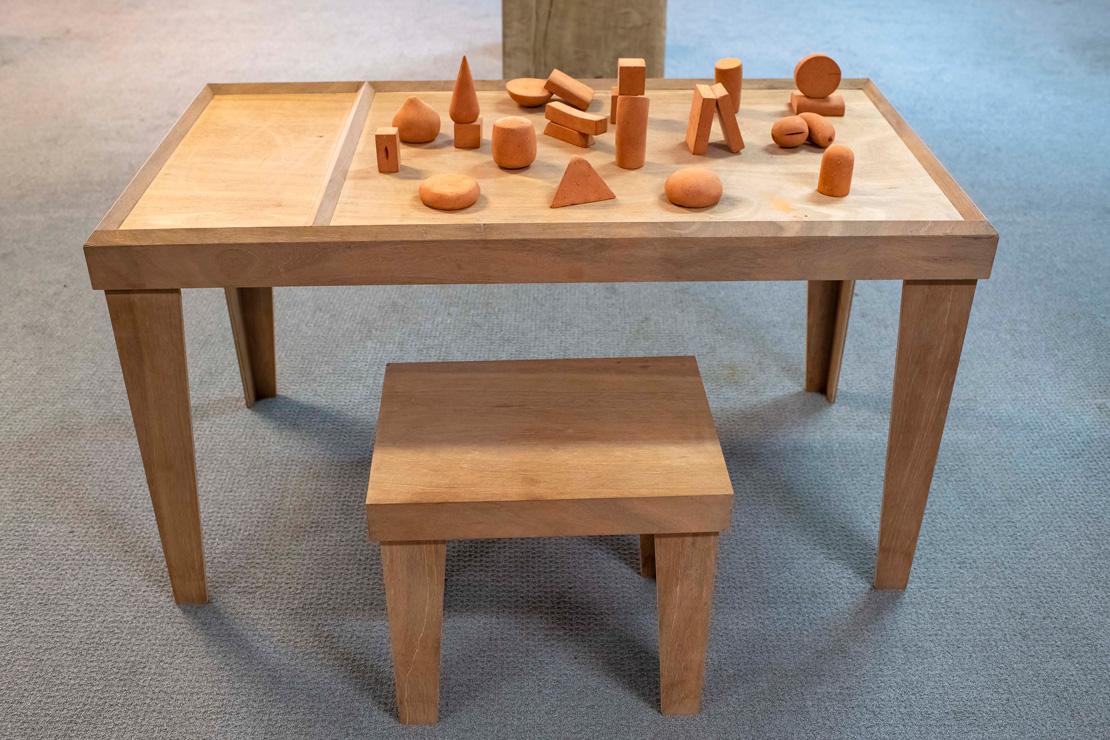 Titel: Playground  Materiaal: hout en gebakken klei  Formaat: 130x69x72cm hoog.  De bezoeker gaat aan de tafel zitten en maakt met een aantal van de 23 kleivormen een compositie(s) , maakt er een foto van en upload die naar een site.